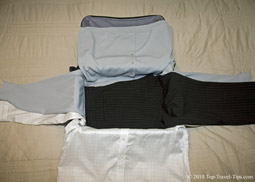 One pair of trousers layed over two shirts as third stage of bundle warpping packing