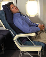 Man sleeping on airplane with inflateable sleeper for back support