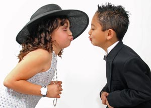 Two kids dressed up about kissing each other