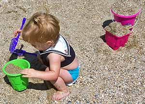 Toddler playing on sandy beach