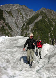 Two people wearing travel clothes on glacier