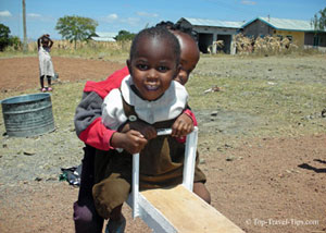 Two kids playing on a seesaw in Tanzania