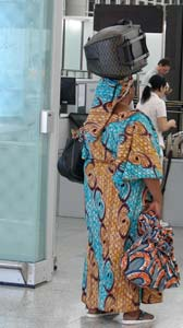 Woman carrying her international traveler luggage on her head