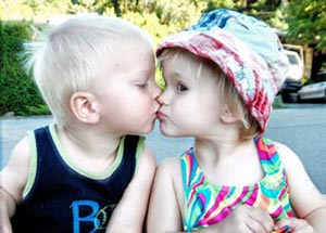 Two travelling toddlers kissing