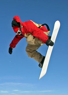 Snowboarder jumping on his snowboard