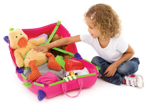 Young girl packing her luggage into Trunki childrens luggage